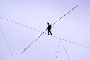A tightrope walker high up in the air.